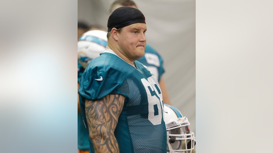 FILE - In this May 29, 2013 file photo, Miami Dolphins guard Richie Incognito watches during an NFL football practice at the Dolphins training facility in Davie, Fla. Suspended Dolphins guard Incognito sent text messages to teammate Jonathan Martin that were racist and threatening, two people familiar with the situation said Monday, Nov. 4, 2013. The people spoke to The Associated Press on condition of anonymity because the Dolphins and NFL haven't disclosed the nature of the misconduct that led to Incognito's suspension. (AP Photo/Wilfredo Lee, File)