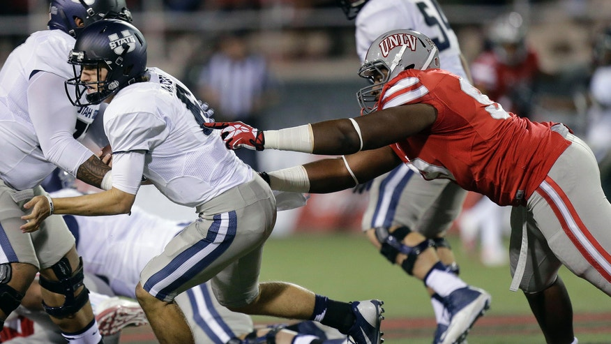 Utah State quarterback Darell Garretson, left, scrambles to get away from UNLV defensive lineman Tyler Gaston in the first quarter of an NCAA college football game Saturday, Nov. 9, 2013, in Las Vegas. (AP Photo/Julie Jacobson)