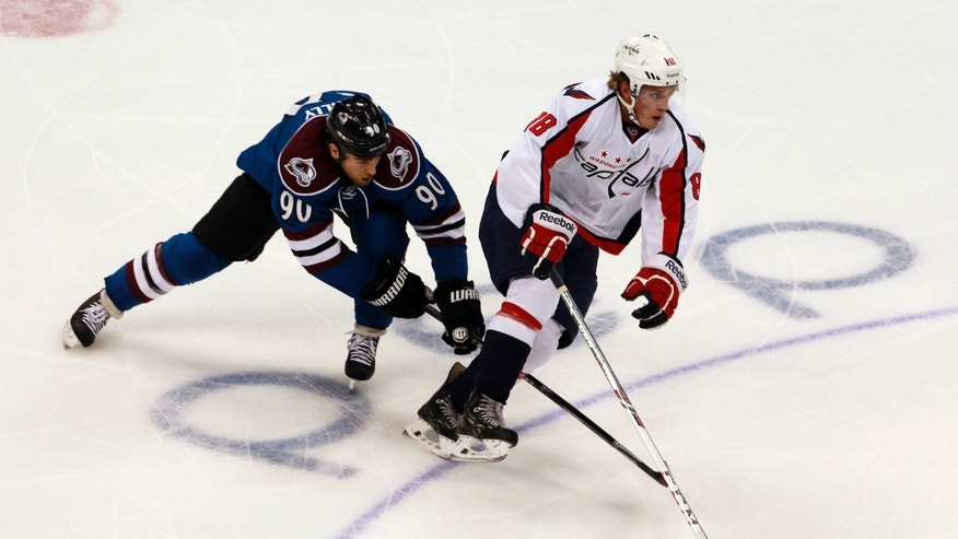 Washington Capitals defenseman Nate Schmidt, right, takes control of the puck at center ice as Colorado Avalanche center Ryan O'Reilly covers in the first period of an NHL hockey game in Denver on Sunday, Nov. 10, 2013. (AP Photo/David Zalubowski)