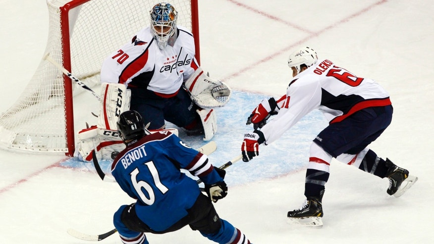Washington Capitals goalie Braden Holtby, back left, stops a shot off the stick of Colorado Avalanche defenseman Andre Benoit, front left, as Capitals defenseman Steve Oleksy covers in the first period of an NHL hockey game in Denver on Sunday, Nov. 10, 2013. (AP Photo/David Zalubowski)