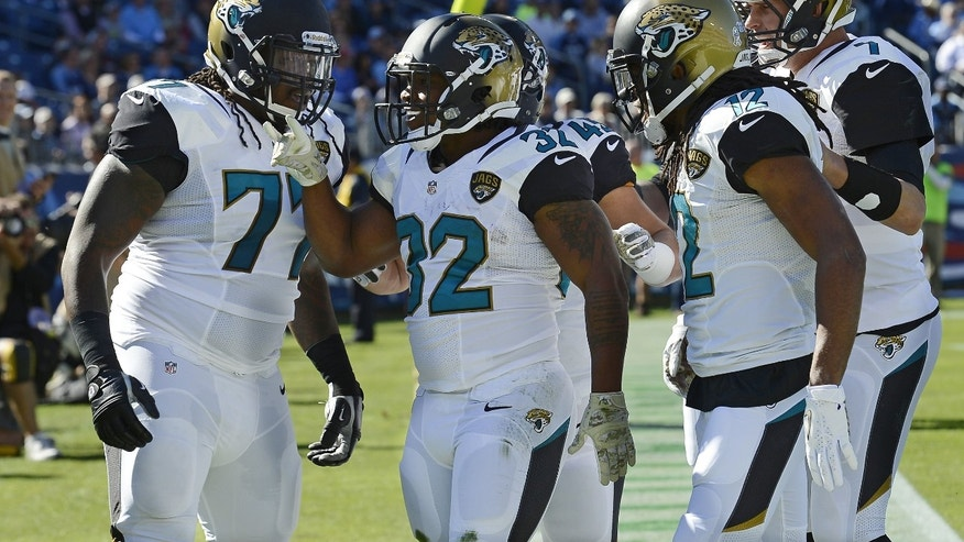 Jacksonville Jaguars running back Maurice Jones-Drew (32) celebrates with Uche Nwaneri (77), Mike Brown (12) and Chad Henne (7) after Jones-Drew scored a touchdown against the Tennessee Titans on a 6-yard run in the first quarter of an NFL football game on Sunday, Nov. 10, 2013, in Nashville, Tenn. (AP Photo/Mark Zaleski)
