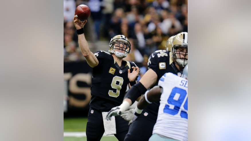 New Orleans Saints quarterback Drew Brees (9) passes under pressure from Dallas Cowboys defensive end George Selvie in the first half of an NFL football game in New Orleans, Sunday, Nov. 10, 2013. (AP Photo/Bill Haber)