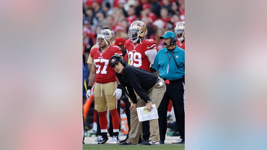 San Francisco 49ers head coach Jim Harbaugh watches from the sideline with linebacker Michael Wilhoite (57) and linebacker Aldon Smith (99) during the fourth quarter of an NFL football game against the Carolina Panthers in San Francisco, Sunday, Nov. 10, 2013. (AP Photo/Ben Margot)