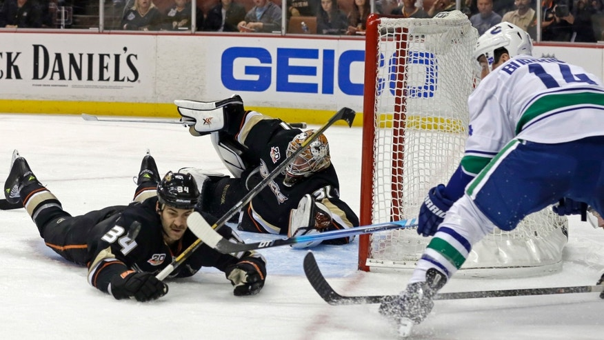 Anaheim Ducks goalie Frederik Andersen (31), of Denmark, and center Daniel Winnik (34) defend as Vancouver Canucks right winger Alexandre Burrows moves in during the first period of an NHL hockey game in Anaheim, Calif., Sunday, Nov. 10, 2013. (AP Photo/Reed Saxon)
