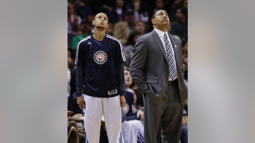Golden State Warriors' Stephen Curry, left, and Warriors coach Mark Jackson watch a replay during the second half of an NBA basketball game against the San Antonio Spurs, Friday, Nov. 8, 2013, in San Antonio. San Antonio won 76-74. Curry did not play because of a left ankle bruise. (AP Photo/Eric Gay)