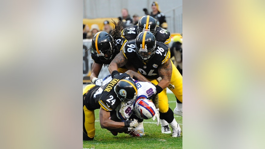 Pittsburgh Steelers cornerback Ike Taylor (24), defensive end Ziggy Hood (96), and outside linebacker Jarvis Jones (95) tackle Buffalo Bills wide receiver Marquise Goodwin (88) during the second half of an NFL football game, Sunday, Nov. 10, 2013, in Pittsburgh. Pittsburgh won 23-10. (AP Photo/Don Wright)