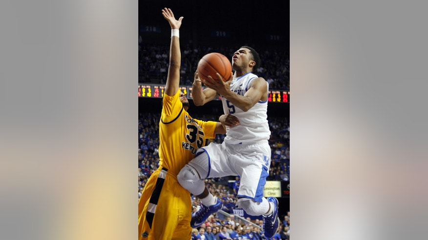 Kentucky's Andrew Harrison (5) shoots under pressure from Northern Kentucky's Deontae Cole (35) during the second half of an NCAA college basketball game, Sunday, Nov. 10, 2013, in Lexington, Ky. (AP Photo/James Crisp)