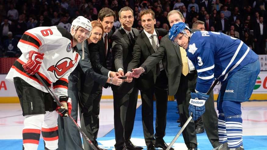 New Jersey Devils defenseman Andy Greene, left to right, Hockey Hall of Fame inductees Geraldine Heaney, Brendan Shanahan, Rob Niedermayer, Chris Chelios, Pittsburgh Penguins GM Ray Shero and Toronto Maple Leafs defenseman Dion Phaneuf pose for a photo before an NHL hockey game between New Jersey Devils and the Toronto Maple Leafs, Friday, Nov. 8, 2013 in Toronto. (AP Photo/The Canadian Press, Frank Gunn)