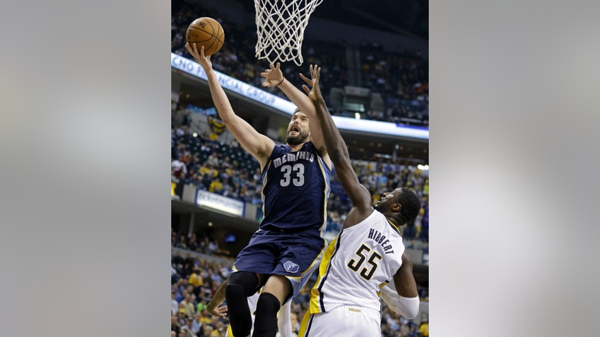 Memphis Grizzlies center Marc Gasol, left, of Spain, goes up for a shot in front of Indiana Pacers center Roy Hibbert in the first half of an NBA basketball game in Indianapolis, Monday, Nov. 11, 2013.  (AP Photo/Michael Conroy)