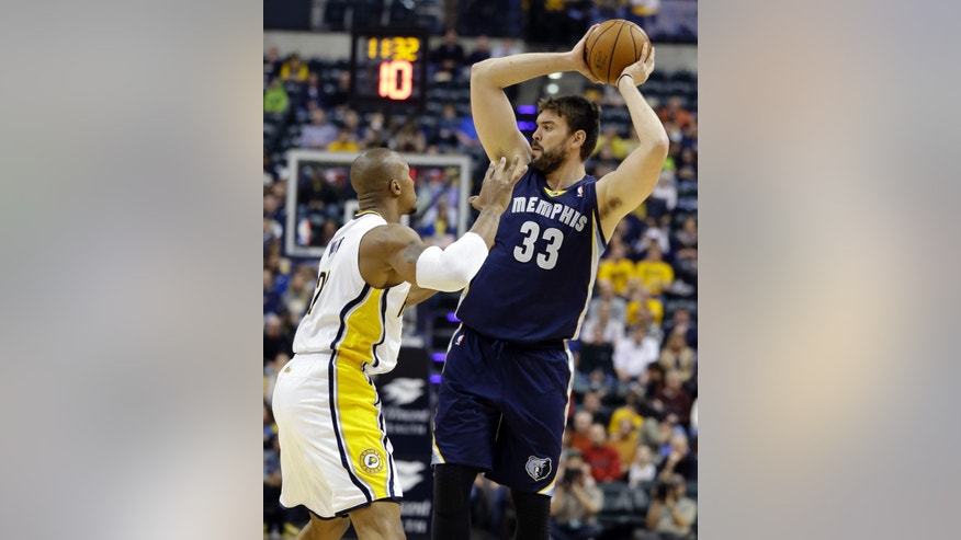 Memphis Grizzlies center Marc Gasol, of Spain, looks to make a pass over Indiana Pacers forward David West in the first half of an NBA basketball game in Indianapolis, Monday, Nov. 11, 2013.  (AP Photo/Michael Conroy)