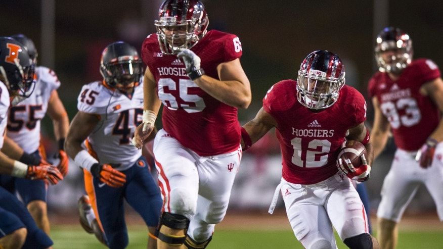 Indiana's Stephen Houston (12) follows closely behind his teammate Wes Rogers (65) as he rushes the ball during the second half of an NCAA college football game, Saturday, Nov. 9, 2013, in Bloomington, Ind. Indiana won 52-35. (AP Photo/Doug McSchooler)