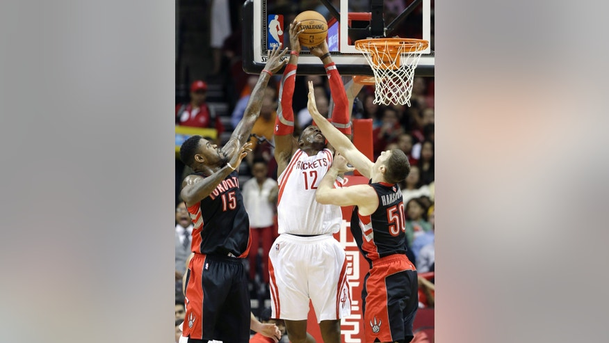Houston Rockets' Dwight Howard (12) goes to the basket between Toronto Raptors Amir Johnson (15) and Tyler Hansbrough (50) in the first half of an NBA basketball game Monday, Nov. 11, 2013, in Houston. (AP Photo/Pat Sullivan)