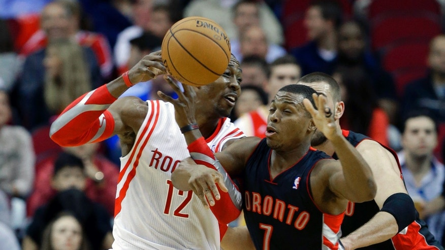 Houston Rockets' Dwight Howard (12) and Toronto Raptors' Kyle Lowry (7) tangle in the first half of an NBA basketball game Monday, Nov. 11, 2013, in Houston. (AP Photo/Pat Sullivan)