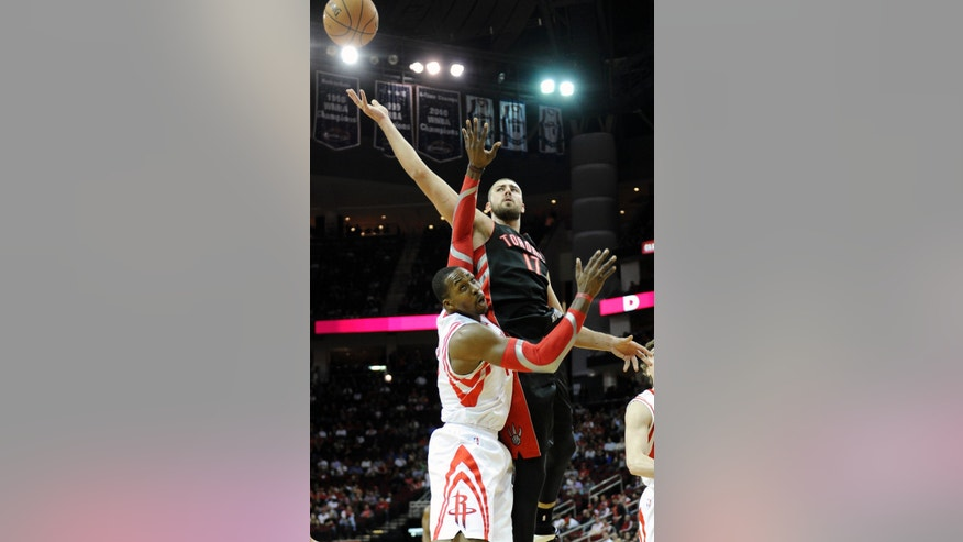 Toronto Raptors' Jonas Valanciunas (17) goes for a rebound over Houston Rockets' Dwight Howard (12) in the first half of an NBA basketball game Monday, Nov. 11, 2013, in Houston. (AP Photo/Pat Sullivan)