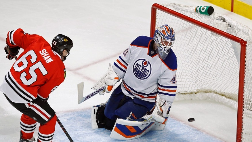 Chicago Blackhawks center Andrew Shaw (65) scores a goal past Edmonton Oilers goalie Devan Dubnyk (40) during the second period of an NHL hockey game on Sunday, Nov. 10, 2013, in Chicago. (AP Photo/Andrew A. Nelles)