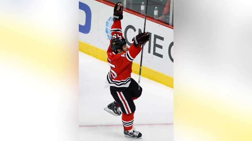 Chicago Blackhawks center Andrew Shaw celebrates his goal past Edmonton Oilers goalie Devan Dubnyk during the second period of an NHL hockey game on Sunday, Nov. 10, 2013, in Chicago. (AP Photo/Andrew A. Nelles)