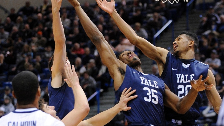 Yale's Nick Victor, left, Brandon Sherrod, second from right,  and Javier Duren, right, fight for a rebound as Connecticut's Omar Calhoun watches during the first half of an NCAA college basketball game, in  Hartford, Conn., on Monday, Nov. 11, 2013. (AP Photo/Fred Beckham)