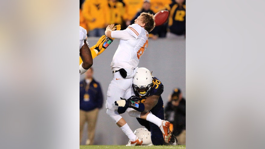 Texas quarterback Case McCoy (6) is sacked by West Virginia's Will Clarke (98) during the second quarter of  an NCAA college football game in Morgantown, W.Va., on Saturday, Nov. 9, 2013. (AP Photo/Christopher Jackson)