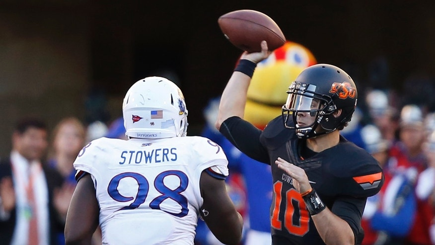Oklahoma State quarterback Clint Chelf passes under pressure from Kansas defender Keon Stowers (98) during the second quarter of an NCAA college football game in Stillwater, Okla., Saturday, Nov. 9, 2013. Oklahoma State won 42-6. (AP Photo/Sue Ogrocki)