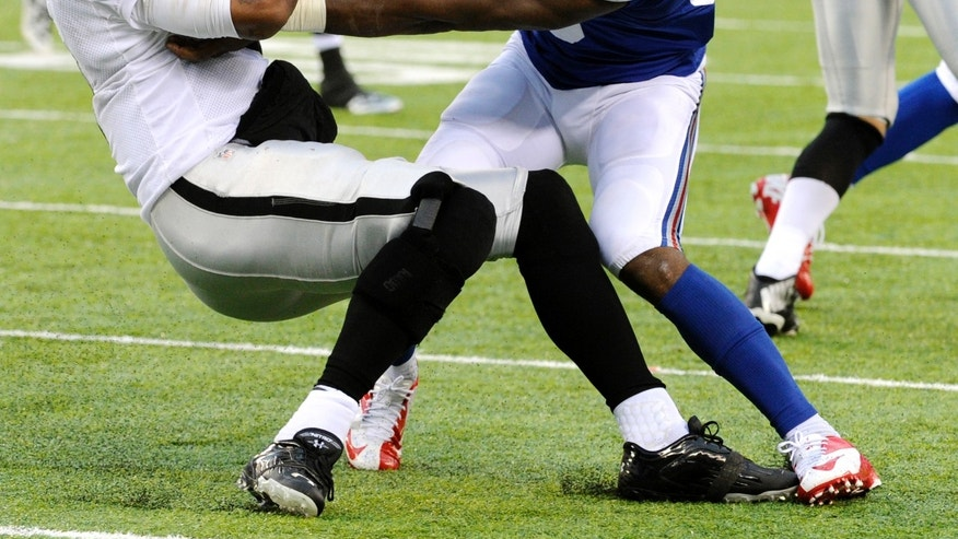 Oakland Raiders quarterback Terrelle Pryor (2) is hit by New York Giants outside linebacker Keith Rivers (55) during the second half of an NFL football game on Sunday, Nov. 10, 2013, in East Rutherford, N.J. (AP Photo/Bill Kostroun)