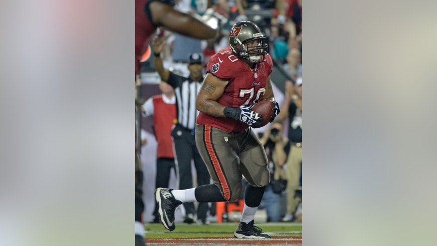 Tampa Bay Buccaneers tackle Donald Penn (70) catches a one-yard touchdown pass against the Miami Dolphins during the first quarter of an NFL football game Monday, Nov. 11, 2013, in Tampa, Fla. (AP Photo/Phelan M. Ebenhack)