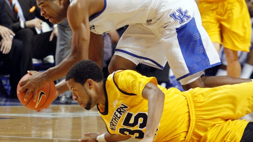 Kentucky's Aaron Harrison, top, gathers up a loose ball next to Northern Kentucky's Deontae Cole (35) during the first half of an NCAA college basketball game on Sunday, Nov. 10, 2013, in Lexington, Ky. (AP Photo/James Crisp)