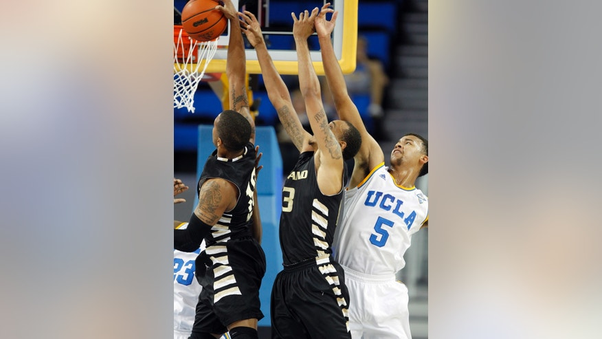 Oakland guard Duke Mondy, left and forward Tommie McCune, center, compete for a rebound with UCLA guard Kyle Anderson (5) in the first half of an NCAA college basketball game Tuesday, Nov. 12, 2013, in Los Angeles. (AP Photo/Alex Gallardo)