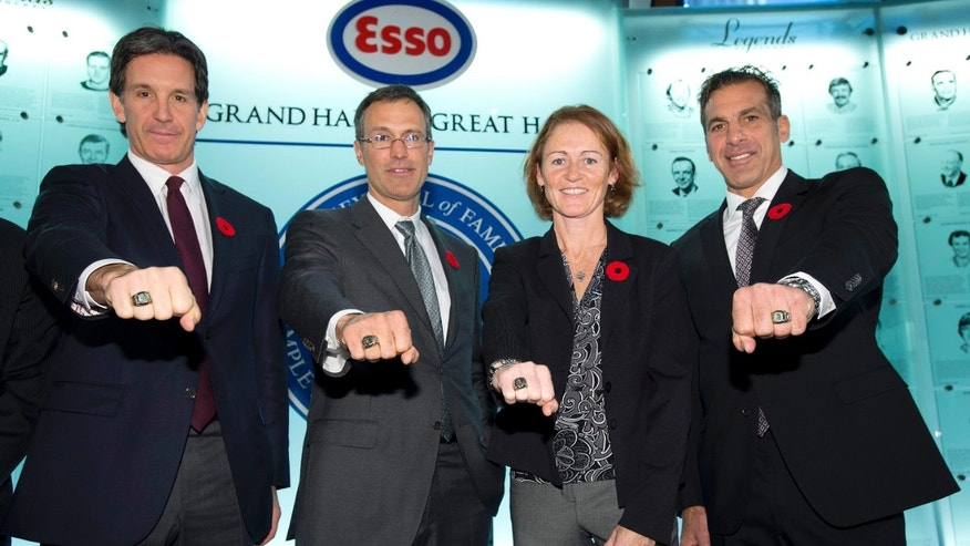 Hockey Hall of Fame inductees, from left, Brendan Shanahan,Scott Niedermayer, Geraldine Heaney and Chris Chelios show off their rings after being presented with them at the Hall in Toronto on Friday, Nov. 8, 2013. (AP Photo/The Canadian Press, Frank Gunn)