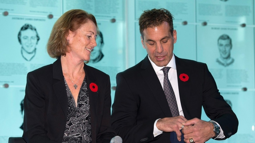 Hockey Hall of Fame inductees Geraldine Heaney and Chris Chelios inspect their rings after being presented with them  at the Hall in Toronto on Friday, Nov. 8, 2013. (AP Photo/The Canadian Press, Frank Gunn)