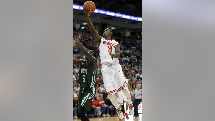 Ohio State's Shannon Scott (3) goes up for a shot over Ohio's Maurice Ndour during the first half of an NCAA college basketball game in Columbus, Ohio, Tuesday, Nov. 12, 2013. (AP Photo/Paul Vernon)