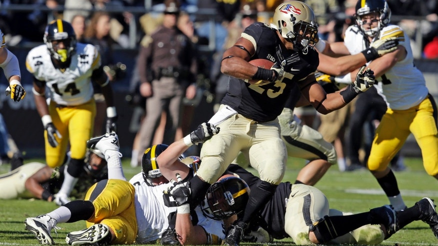Purdue running back Brandon Cottom, top, is tackled by Iowa defensive lineman Louis Trinca-Pasat during the first half of an NCAA college football game in West Lafayette, Ind., Saturday, Nov. 9, 2013. (AP Photo/Michael Conroy)