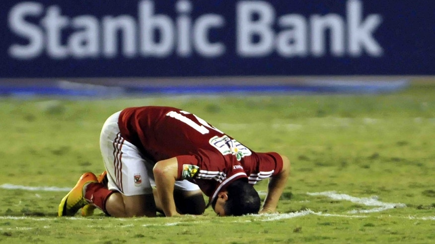 Egyptian Al Ahly club player Ahmed Abdul Zaher, kneels after winning South Africa's Orlando Pirates, at the Arab Contractors stadium in Cairo, Egypt, Sunday, Nov. 10, 2013. Egypt's Al Ahly retained its African Champions League title by beating South Africa's Orlando Pirates 2-0 on Sunday, with the match being played amid heavy security and preceded by clashes between fans and police outside the stadium in Cairo.  (AP Photo/Osama Abdel Naby)