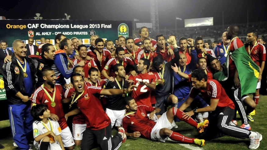 Egyptian Al Ahly club team players pose for a photograph after winning South Africa's Orlando Pirates, at the Arab Contractors stadium in Cairo, Egypt, Sunday, Nov. 10, 2013. Egypt's Al Ahly retained its African Champions League title by beating South Africa's Orlando Pirates 2-0 on Sunday, with the match being played amid heavy security and preceded by clashes between fans and police outside the stadium in Cairo.  (AP Photo/Osama Abdel Naby)