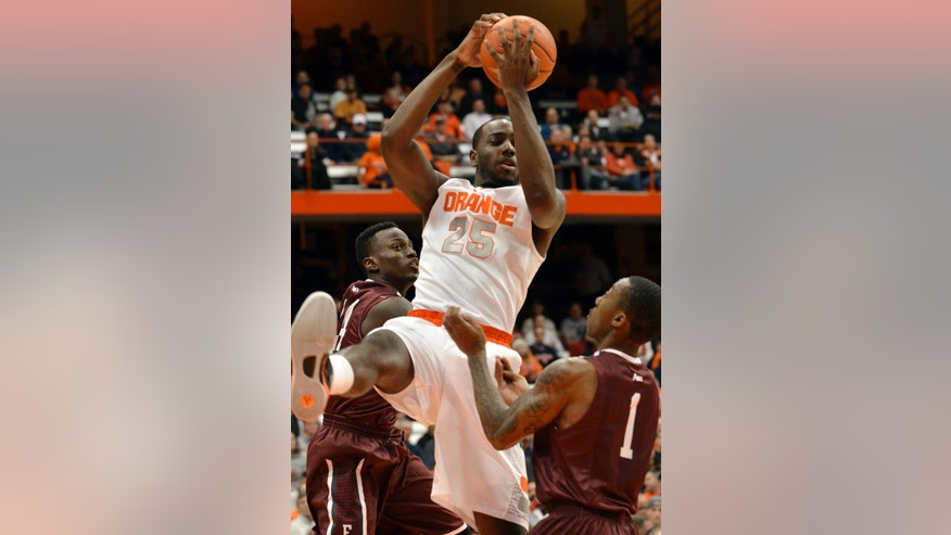 Syracuse's Rakeem Christmas (25) grabs a rebound against Fordham's Bryan Smith, left, and Mandell Thomas during the first half of an NCAA college basketball game in Syracuse, N.Y., Tuesday, Nov. 12, 2013. (AP Photo/Kevin Rivoli)