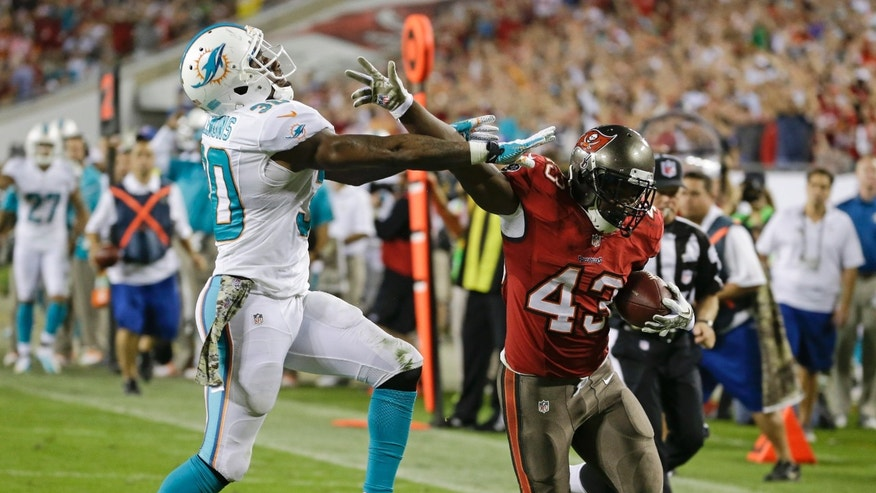 Tampa Bay Buccaneers running back Bobby Rainey (43) is pushed out of bounds by Miami Dolphins strong safety Chris Clemons, left, after a 31-yard run during the fourth quarter of an NFL football game in Tampa, Fla., Tuesday, Nov. 12, 2013. Rainey scored a touchdown on the next play from 1-yard out.(AP Photo/John Raoux)