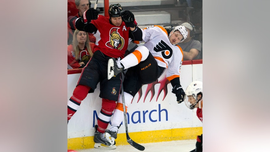 Ottawa Senators defenseman Marc Methot, left, collides along the boards with Philadelphia Flyers defenseman Mark Streit during the second period of an NHL hockey game Tuesday, Nov. 12, 2013, in Ottawa, Ontario. (AP Photo/The Canadian Press, Adrian Wyld)