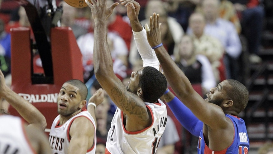 Portland Trail Blazers forward LaMarcus Aldridge, left, battles for a rebound with Detroit Pistons forward Greg Monroe during the first half of an NBA basketball game in Portland, Ore., Monday, Nov. 11, 2013.  At far left in background is Trail Blazers forward Nicolas Batum, from France.(AP Photo/Don Ryan)