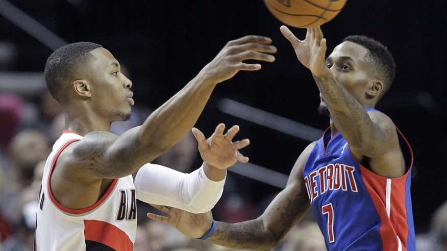 Portland Trail Blazers guard Damian Lillard, left, passes off against Detroit Pistons guard Brandon Jennings during the first half of an NBA basketball game in Portland, Ore., Monday, Nov. 11, 2013. (AP Photo/Don Ryan)
