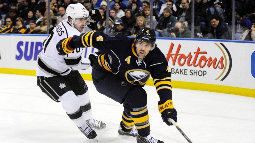 Los Angeles Kings center Mike Richards, left, chases Buffalo Sabres defenseman Jamie McBain (4) as he moves up ice during the second period of an NHL hockey game in Buffalo, N.Y., Tuesday, Nov. 12, 2013. (AP Photo/Gary Wiepert)
