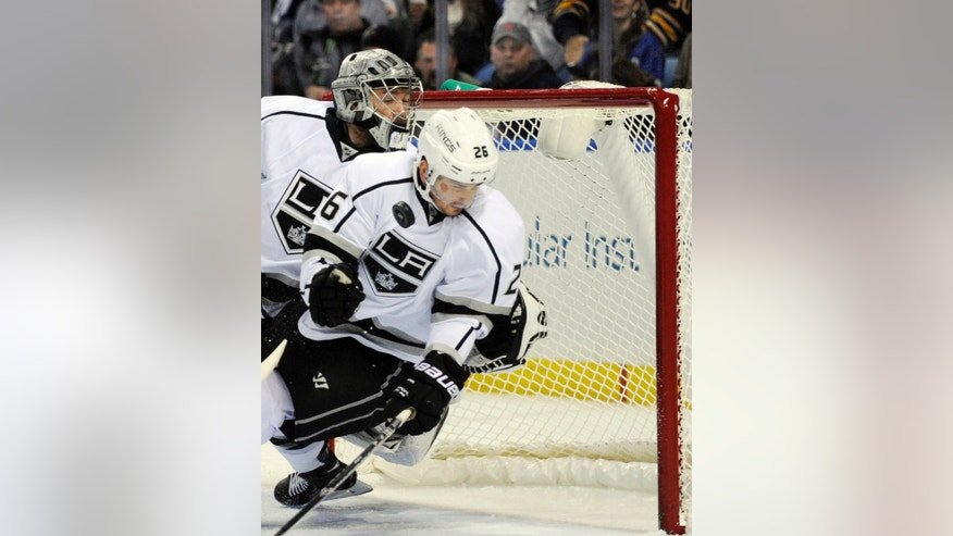 Los Angeles Kings goaltender Jonathan Quick, left, watches defenseman Slava Voynov, right, of Russia, block the puck on a Buffalo Sabres' shot during the first period of an NHL hockey game in Buffalo, N.Y., Tuesday, Nov. 12, 2013. (AP Photo/Gary Wiepert)