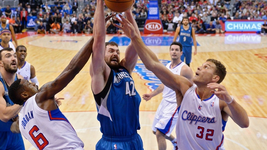 Minnesota Timberwolves forward Kevin Love, center, battles for a rebound with Los Angeles Clippers center DeAndre Jordan, left, and forward Blake Griffin during the first half of an NBA basketball game, Monday, Nov. 11, 2013, in Los Angeles. (AP Photo/Mark J. Terrill)