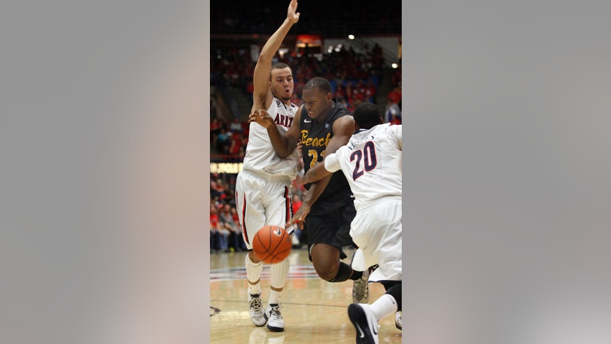 Long Beach State's Christian Griggs-Williams, middle, tries to dribble between Arizona's Gabe York, left, and Jordin Mayes (20) in the first half of an NCAA college basketball game, Monday, Nov. 11, 2013 in Tucson, Ariz.  (AP Photo/Wily Low)