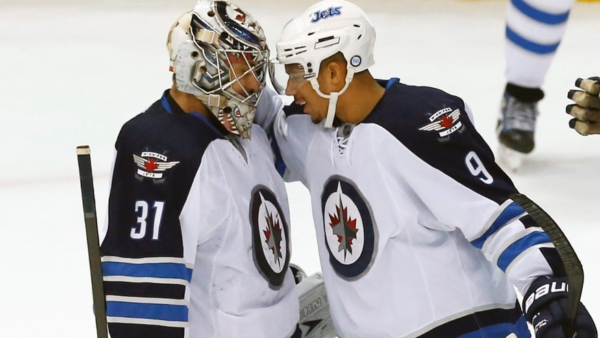 Winnipeg Jets goalie Ondrej Pavelec (31), of the Czech Republic, is congratulated by Winnipeg Jets wing Evander Kane (9) after a NHL hockey game against the Detroit Red Wings in Detroit, Tuesday, Nov. 12, 2013. Winnipeg won 3-2 in a shootout. (AP Photo/Paul Sancya)