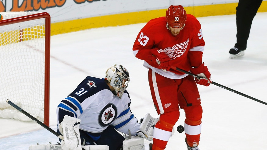 Winnipeg Jets goalie Ondrej Pavelec (31), of the Czech Republic, stops a shot as Detroit Red Wings left wing Johan Franzen (93), of Sweden, tries to redirect the puck in the third period of an NHL hockey game in Detroit, Tuesday, Nov. 12, 2013. (AP Photo/Paul Sancya)