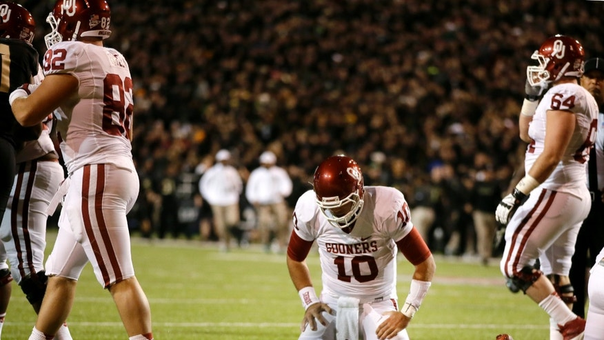 Oklahoma quarterback Blake Bell (10) kneels over the ball after being stopped short of the goal on a fourth-and-goal play in the first half of an NCAA college football game against Baylor, Thursday, Nov. 7, 2013, in Waco, Texas. Oklahoma's Brannon Green (82) and Gabe Ikard (64) walk toward the sideline in the 41-12 Baylor win.  (AP Photo/Tony Gutierrez)