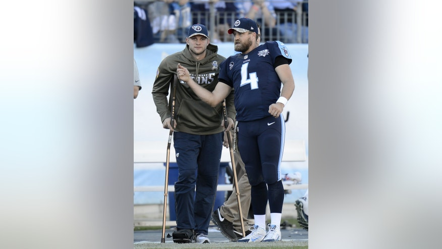 Tennessee Titans quarterback Jake Locker, left, watches from the sideline as he talks with fellow quarterback Ryan Fitzpatrick (4) in the fourth quarter of an NFL football game on Sunday, Nov. 10, 2013, in Nashville, Tenn. Locker injured his foot earlier in the game. (AP Photo/Mark Zaleski)