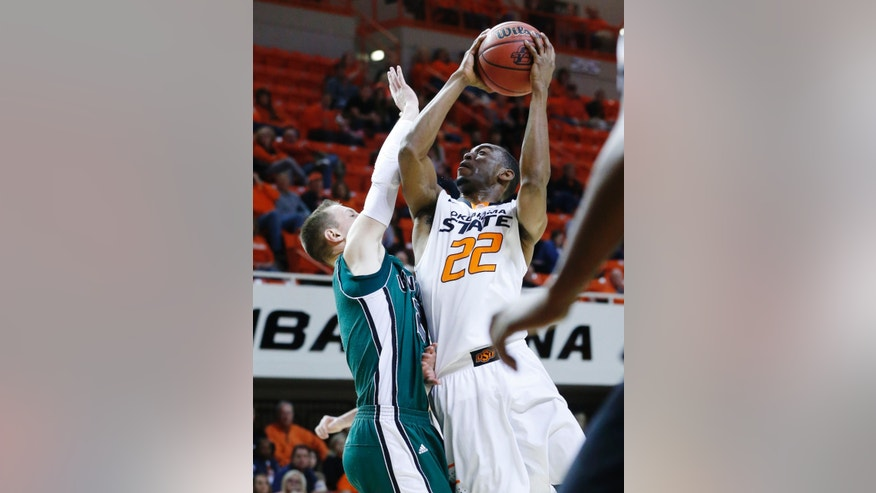 Oklahoma State wing Markel Brown shoots in front of Utah Valley guard Hayes Garrity in the first half of an NCAA college basketball game in Stillwater, Okla., Tuesday, Nov. 12, 2013. (AP Photo/Sue Ogrocki)
