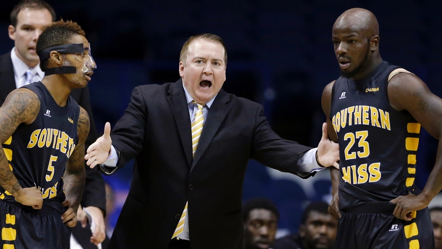 Southern Mississippi head coach Donnie Tyndall, center, talks to guard Neil Watson, left, and guard Jerrold Brooks during the first half of an NCAA college basketball game against DePaul in Rosemont, Ill., Wednesday, Nov. 13, 2013. (AP Photo/Nam Y. Huh)