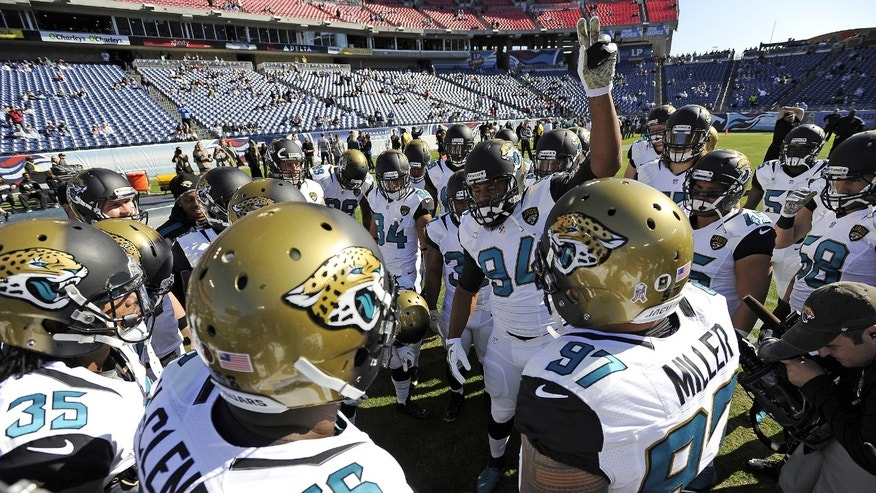 FILE - In this Nov. 10, 2013 file photo, Jacksonville Jaguars defensive end Jeremy Mincey (94) fires up his teammates before an NFL football game against the Tennessee Titans in Nashville, Tenn. As TV ratings stay strong, the number of people showing up for games _ even in places that are traditionally hot tickets _ is dwindling.  (AP Photo/Mark Zaleski, File)