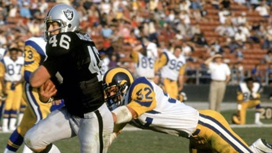 Todd Christensen avoids a tackle from a Rams defender during a game in 1982. (AP)